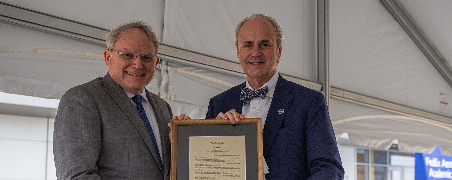 Kent State President Todd Diacon (right) hands a framed resolution from the Kent State Board of Trustees that names the FedEx Aeronautics Academic Center to Don Dillman (left), senior vice president of flight operations for FedEx.