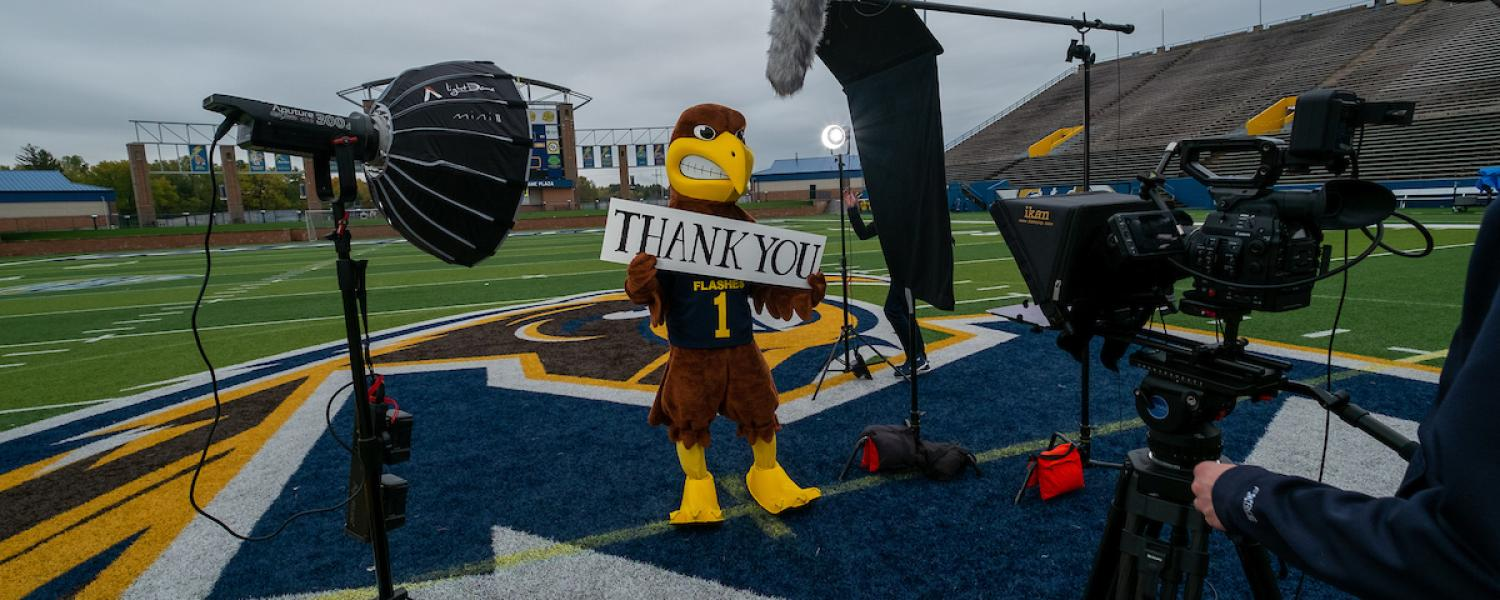 "Kent State's mascot Flash holds a ""Thank You"" sign while filming a scene for a commercial honoring the university's front line employees."