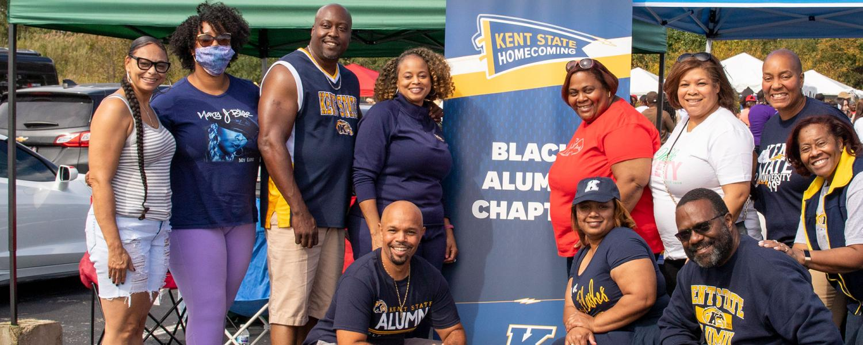 Photo of alumni at Homecoming banner