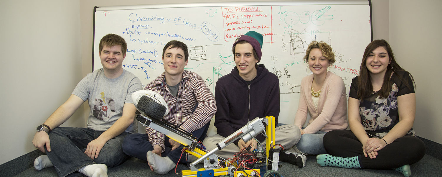 Members of the Kent State Robotics Team sit by a competition robot which had to throw a football and be able to scoop up golf balls while completing other tasks.