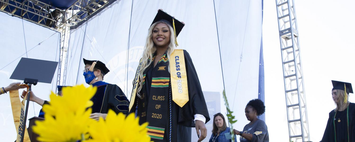 A member of Kent State's Class of 2020 crosses the stage during the special commencement ceremony held for the class during Homecoming 2021.