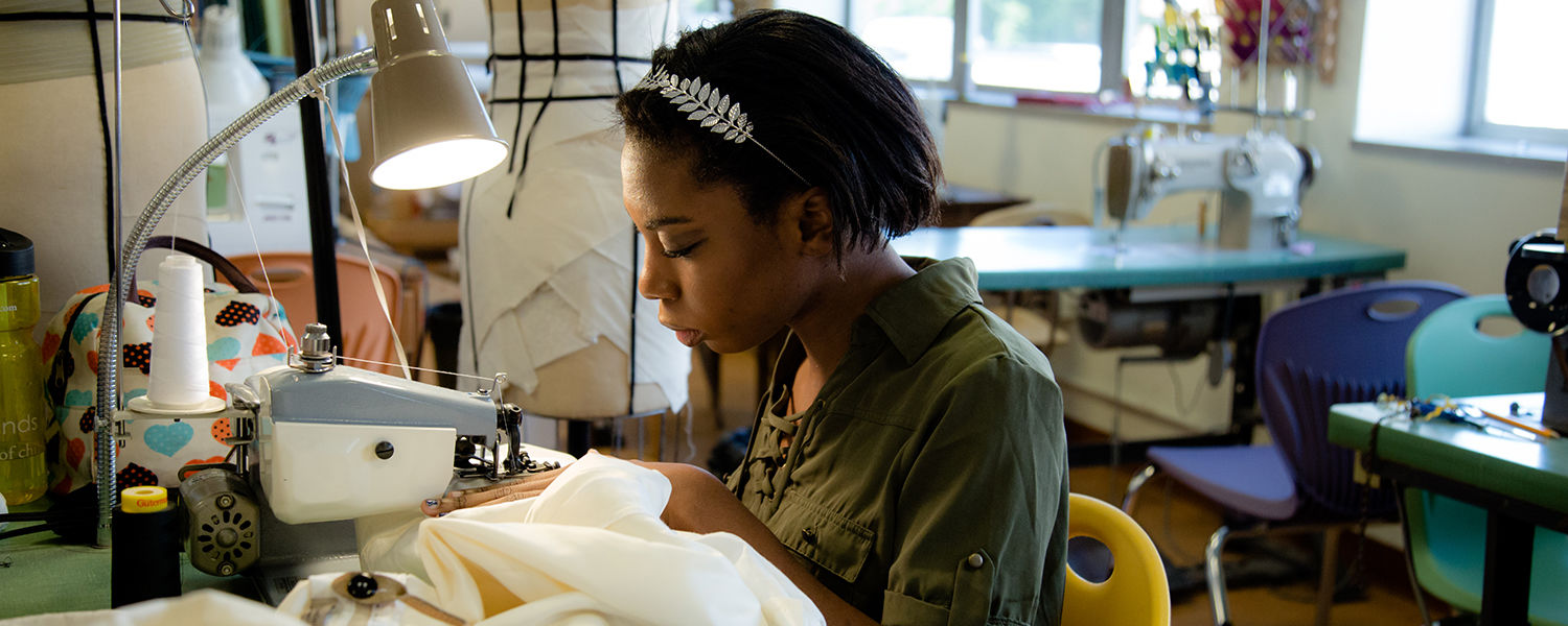 """Madisyn Fluitt, design intern for the Porthouse Theatre and a rising senior majoring in costume design, stitches a costume for """"9 to 5."""""""
