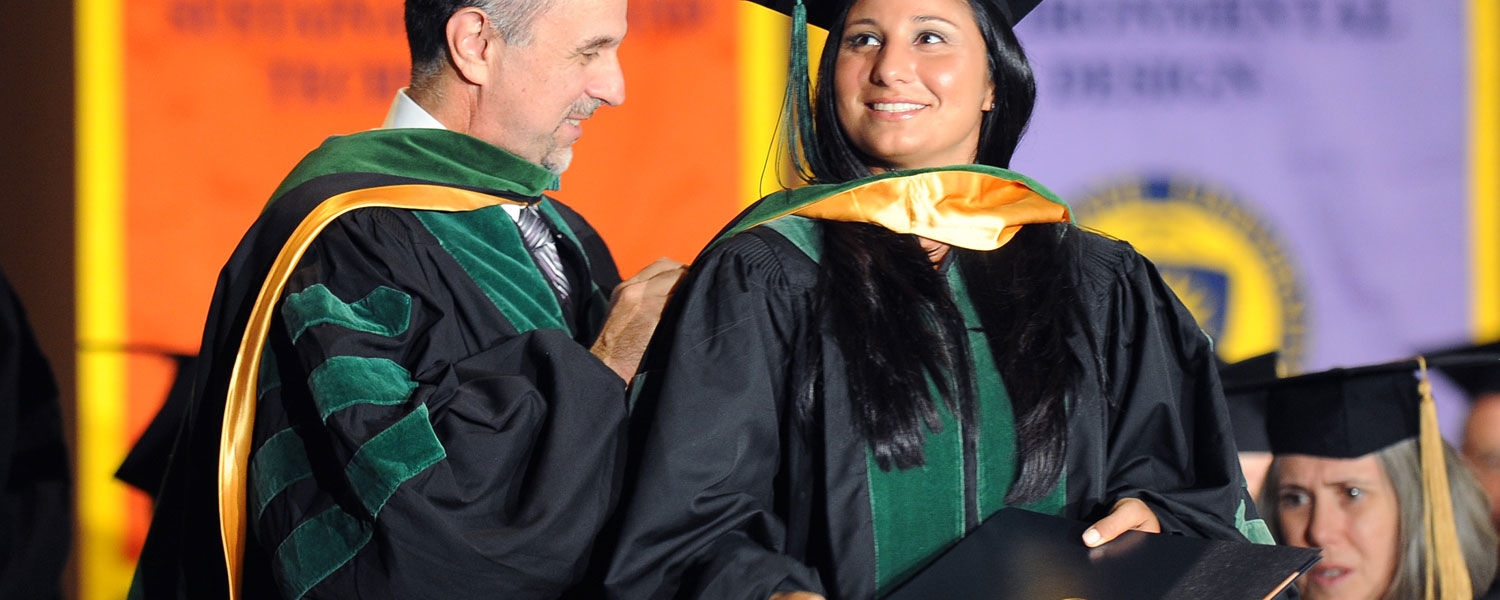 Kent State College of Podiatric Medicine student Christina Schilero is hooded by her father, Dr. John Schilero, during the college's commencement ceremony.