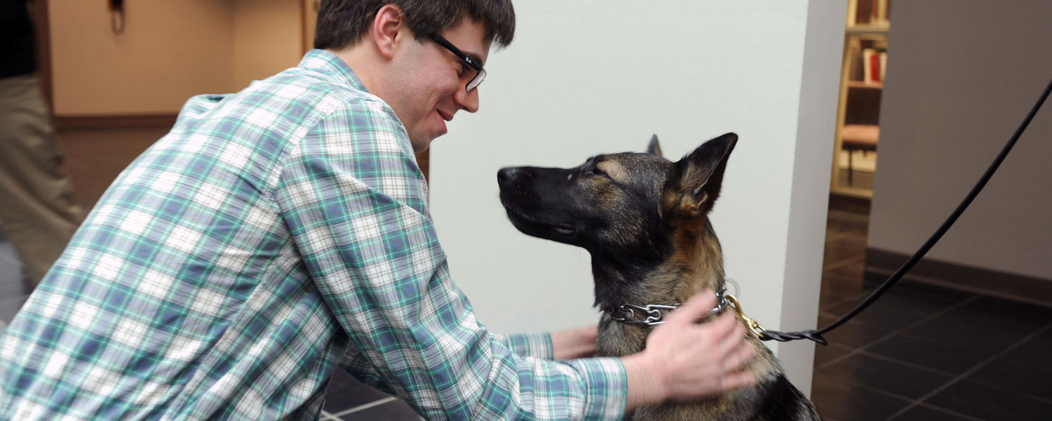 Kent State police dog Coco greets a staff member on the first floor of Rockwell Hall.