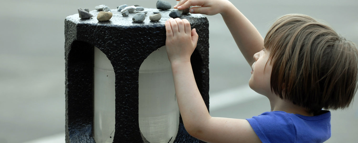 The daughter of a Kent State faculty member lays a stone on one of the concrete lanterns in the lot near Taylor Hall. The placing of stones on a memorial is a Jewish tradition.