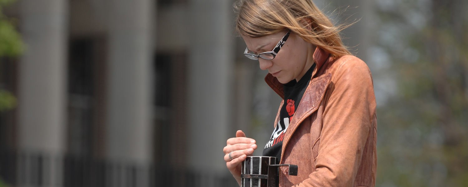 A Kent State University student stands vigil around noon on May 4 in the parking lot near Taylor Hall.