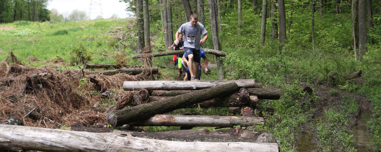 Runners encounter the log jam obstacle during the 2014 FlashDash.