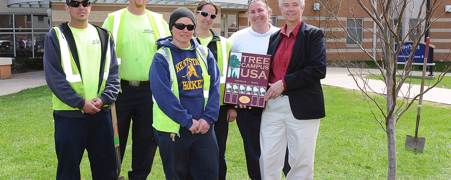 Heather White (right), grounds manager of University Facilities Management at Kent State, displays Kent State's Tree Campus USA designation following the 2014 Arbor Day tree planting ceremony in the courtyard of Centennial A and B. She is pictured with gr
