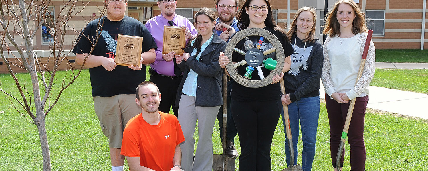 """Kent State students show off their plaques from the residence hall challenge during this year's RecycleMania recycling competition with Engleman Hall winning first place and Centennial A and B receiving """"most improved."""" The students also display the Bragg"""