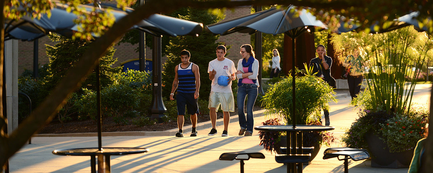 Kent State students walk through the Risman Plaza, framed by trees, on a warm spring afternoon.