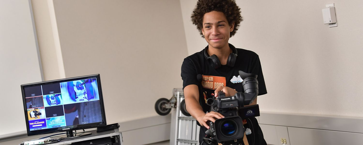Firestone Community Learning Center student learns to operate a video camera during a class in Franklin Hall in the Kent State University College of Communication and Information.