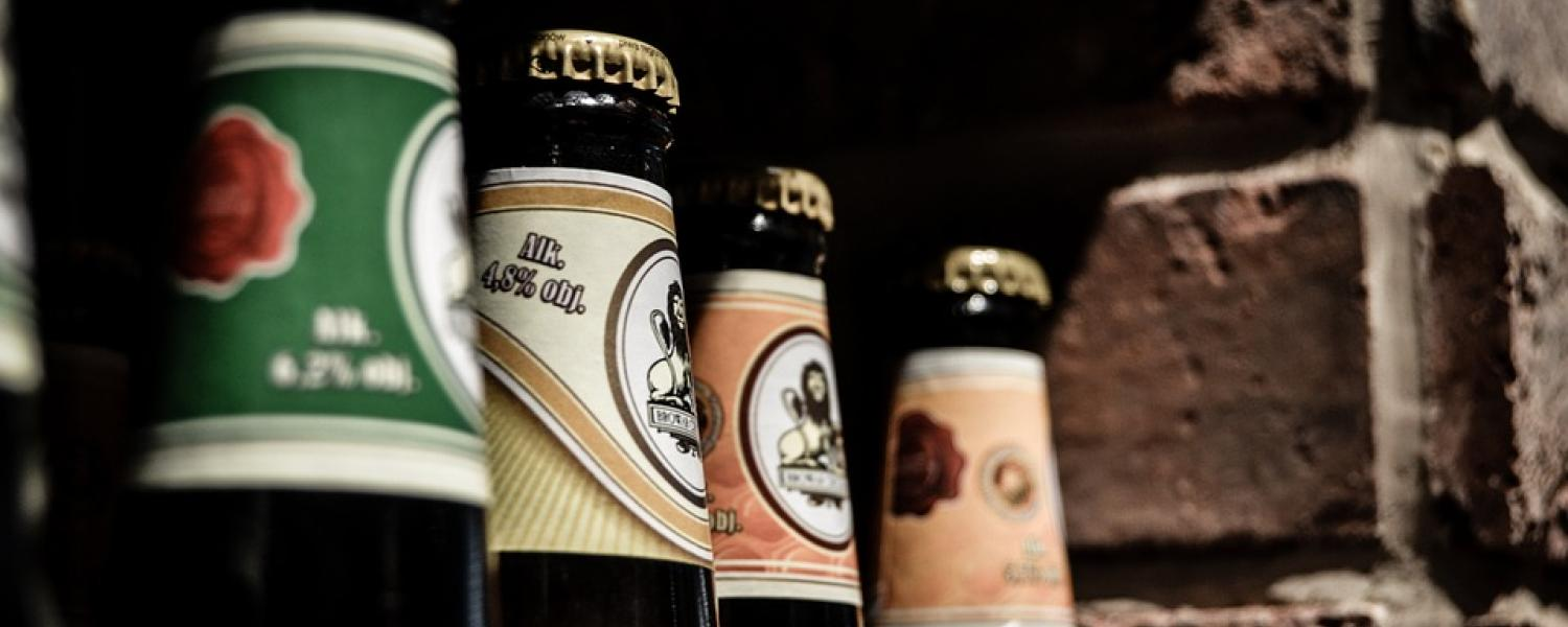 Photo of the necks of beer bottles lined up at an angle