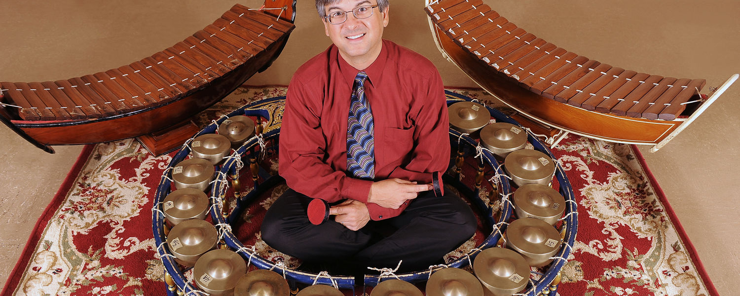 Andrew Shahriari, who has been selected as Kent State's Scholar of the Month, sits in a khong wong yai (big gong circle) with two ranad eks (lead xylophones) in the background in a School of Music classroom.