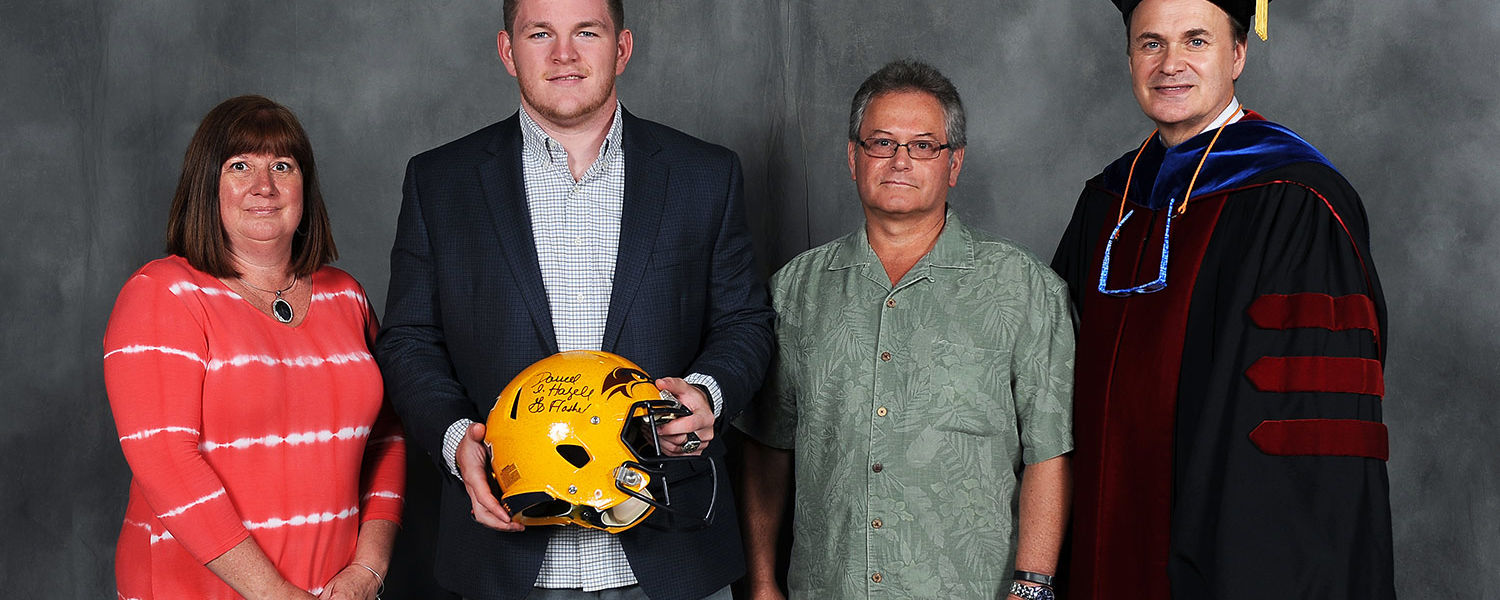Graduating Kent State football player Kyle Payton holds the helmet the team wore at the 2013 GoDaddy.com Bowl. The helmet was presented to Payton by season ticket holders Patty and Dale Hartshorn.