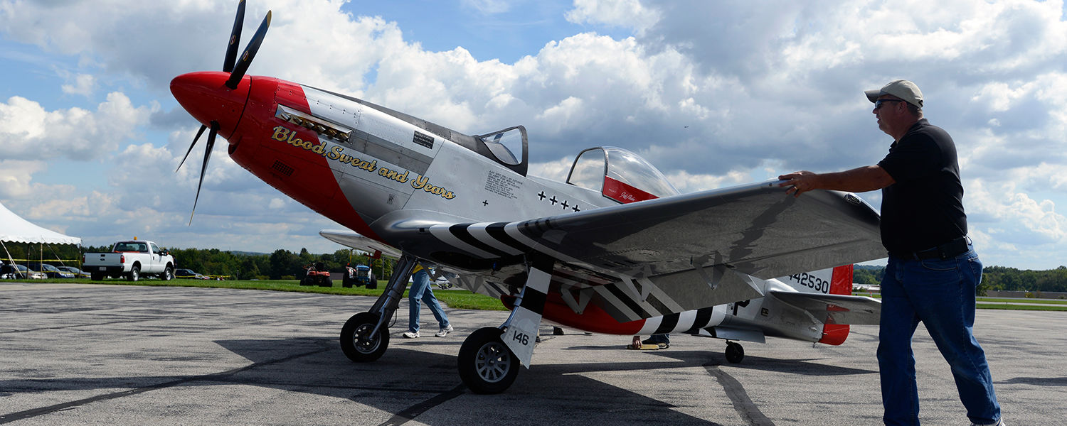 Ground crews guide a WWII-era P-51 Mustang into position for viewing at the Aviation Heritage Fair at the Kent State University Airport.