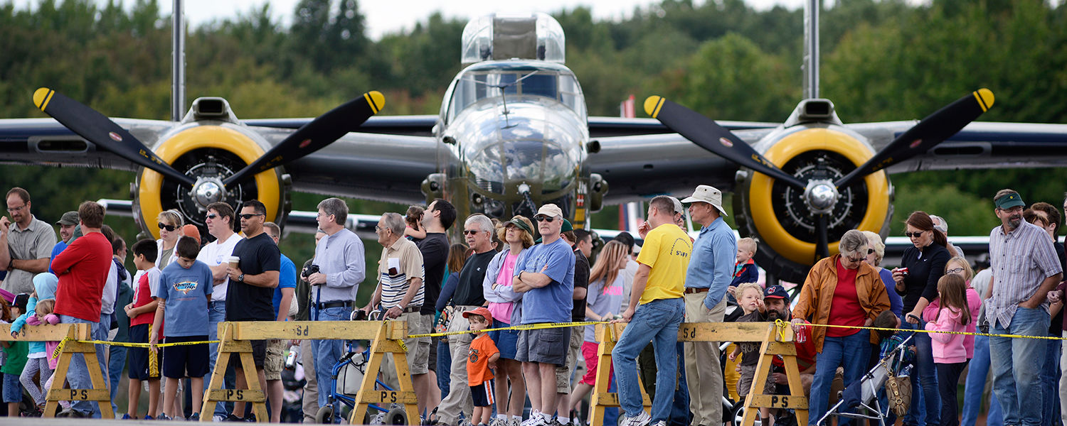 Spectators line the runway to watch incoming aircraft touch down during the Aviation Heritage Fair at the Kent State University Airport.