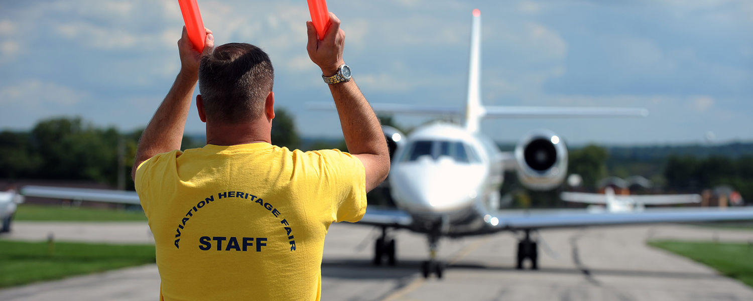 An airport staff member guides an incoming aircraft into position during a past Aviation Heritage Fair at the Kent State University Airport.