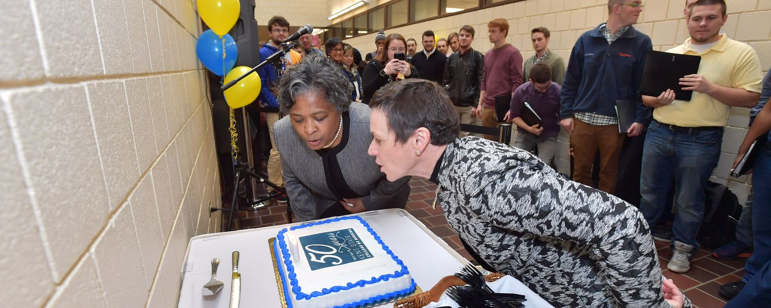Kent State University President Beverly Warren (right) and Dean Barbara Broome, Ph.D., RN, FAAN, blow out candles at the College of Nursing's 50th birthday party Monday afternoon.