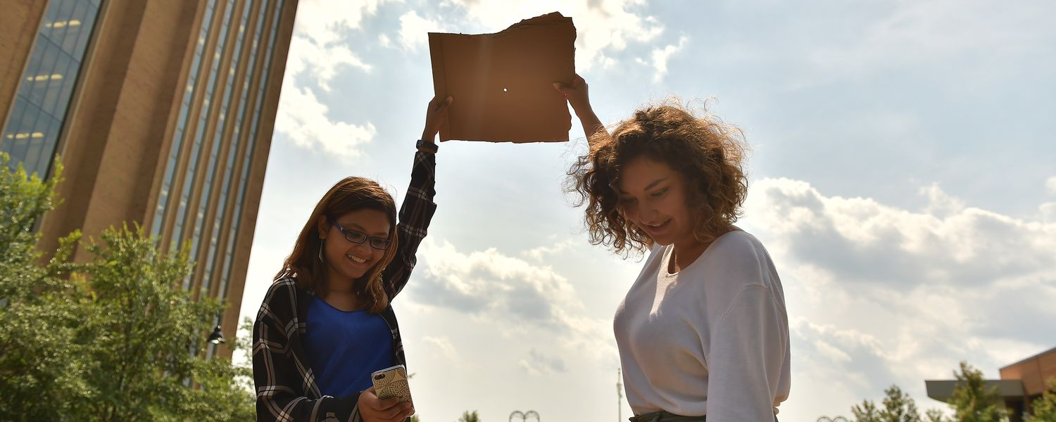 Kent State students use cardboard boxes to view the solar eclipse.