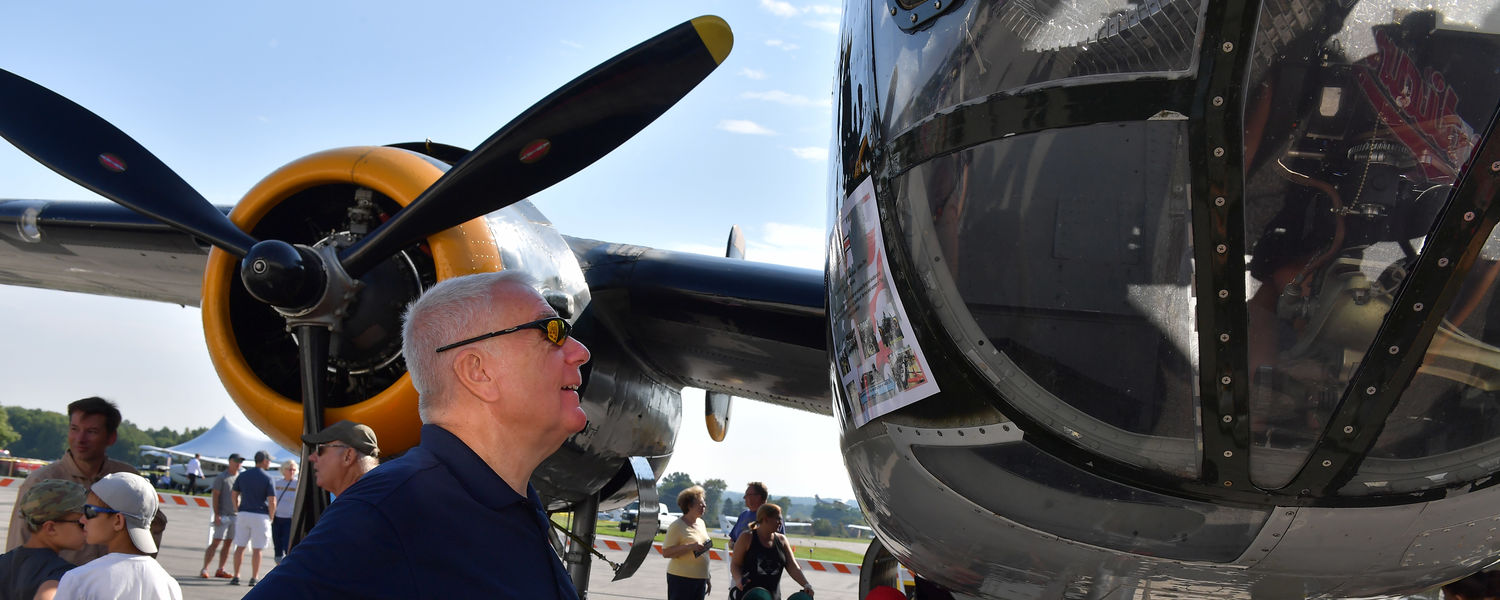 Robert Sines Jr., interim dean of Kent State's College of Aeronautics and Engineering, reads all about a B-25 Mitchell during the 2016 Kent State University Aeronautics Fair.