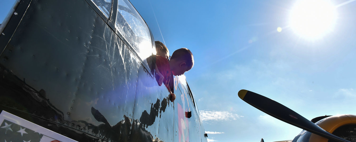 A child looks out the window of a B-25 Mitchell during the 2016 Kent State University Aeronautics Fair.