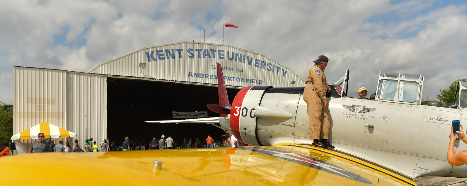 The pilot of a Commemorative Air Force trainer talks to a child about the plane during the 2016 Kent State University Aeronautics Fair.