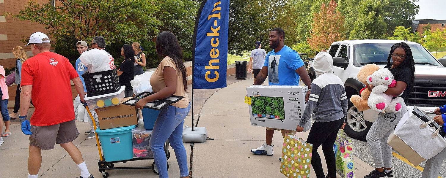 A Kent State staff member helps a family move into Centennial Court A.