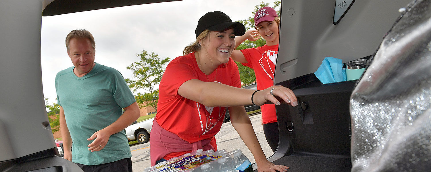 Kent State students volunteering as Movers and Groovers help unload gear from the back of an incoming freshman's SUV.