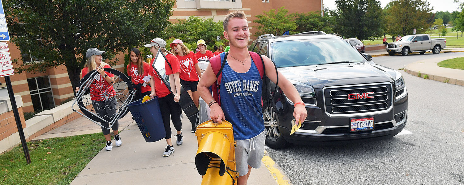 An incoming Kent State freshman hauls his own personal traffic light into his residence hall while Mover and Groover volunteers carry the rest of his belongings.