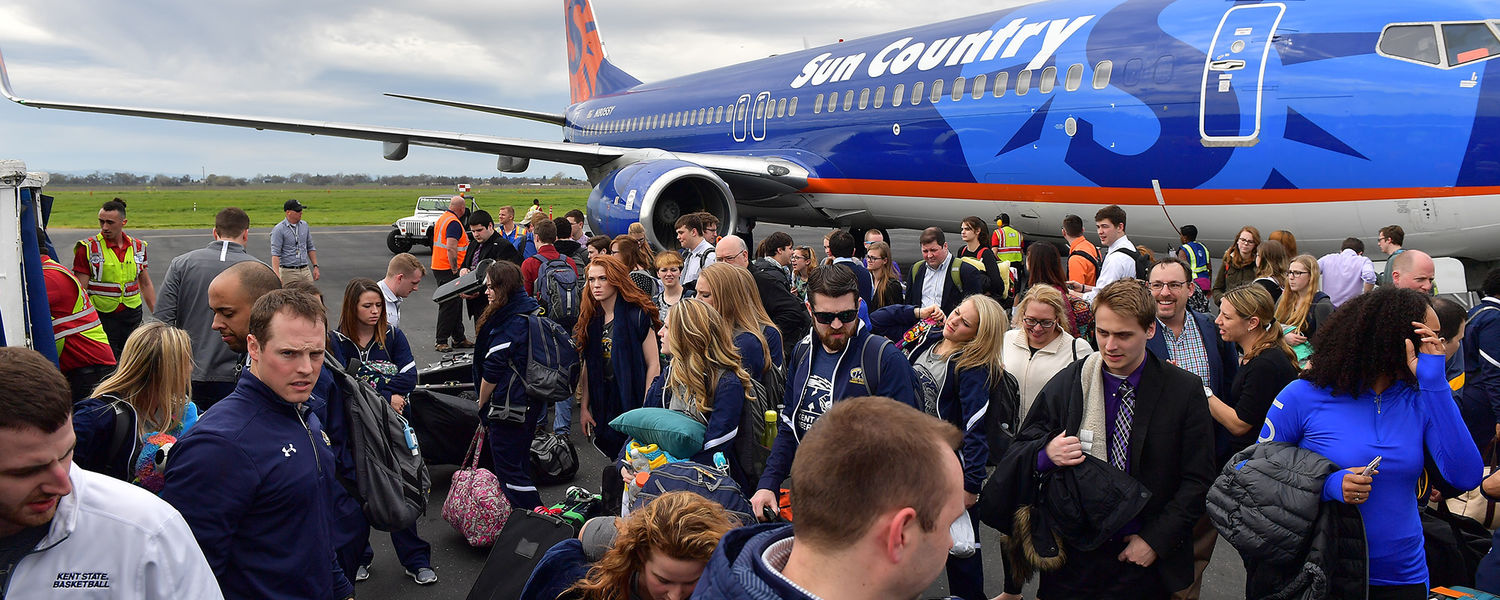 Basketball team members along with band and cheer team arrive in California