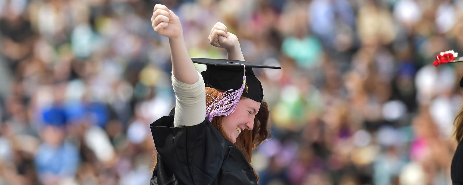 A new Kent State graduate celebrates as she goes down the ramp from the stage.