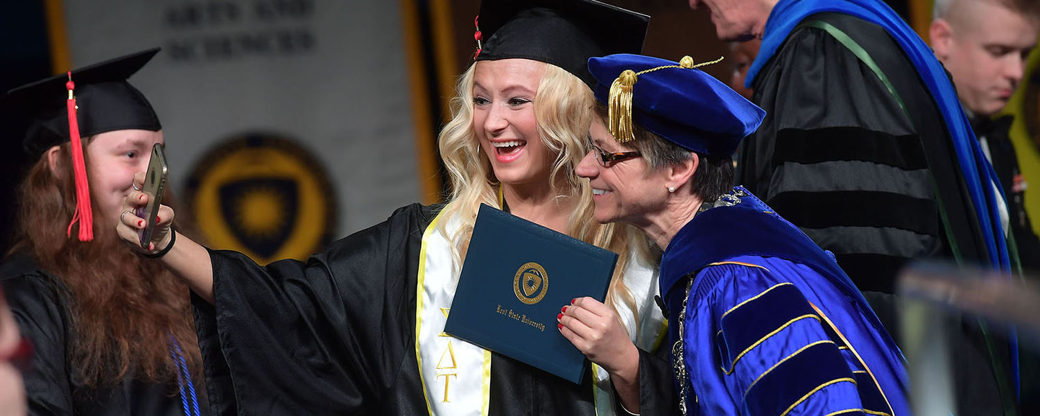 A new graduate takes a selfie with Kent State President Beverly Warren on stage during Commencement.