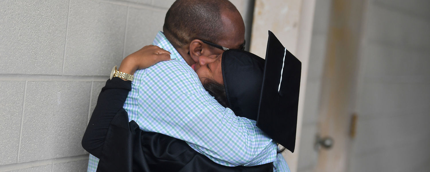 A father hugs his daughter following Kent State's 2018 One University Commencement.