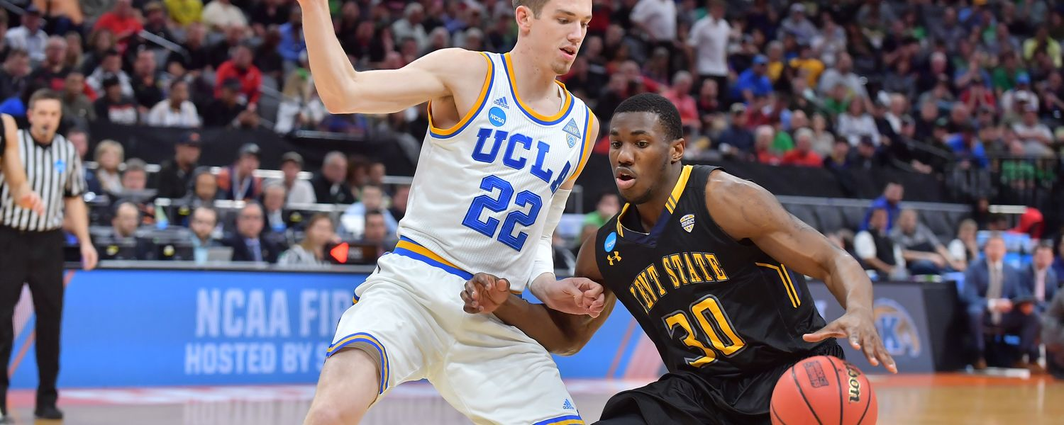 Kent State guard Deon Edwin dribbles past a UCLA Bruin in the first-round game of the NCAA Men's Basketball Tournament.