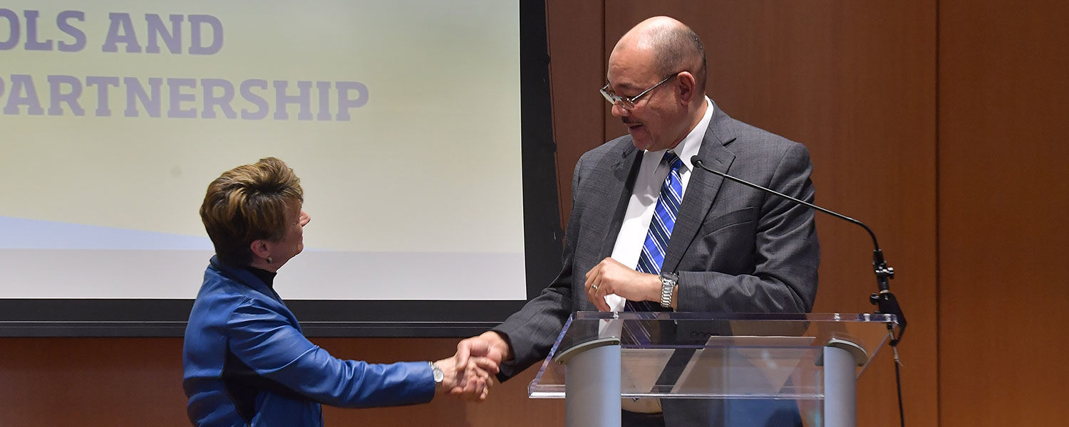 Kent State President Beverly J. Warren shakes hands with Akron Public Schools Superintendent David James.