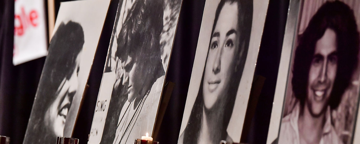 Portraits of the four students killed on May 4, 1970, sit on chairs on stage in the Kent Student Center Ballroom.