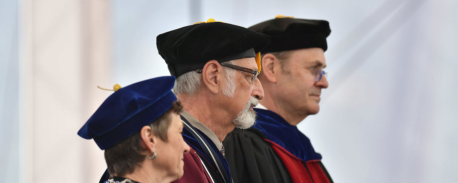 Kent State President Beverly Warren, Distinguished Professor of Human Evolutionary Studies C. Owen Lovejoy and Kent State Senior Vice President for Academic Affairs and Provost Todd Diacon listen as Lovejoy's accomplishments are read.