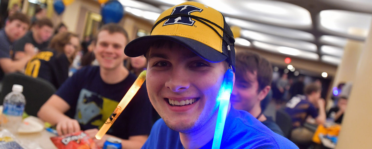 A fan of the Kent State Golden Flashes wears glow sticks while waiting to get his T-shirts.