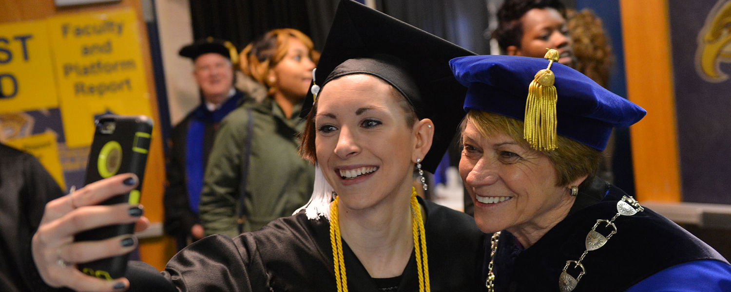 Kent State President Beverly Warren takes a selfie with a new graduate prior to the Fall 2015 Commencement ceremony.