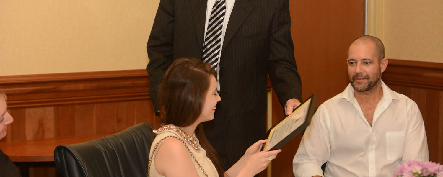 Kent State student Zoë Burch is presented with a certificate from Andrew Stefanik, regional coordination unit supervisor of Ohio Homeland Security Strategic Analysis and Information Center while her dad, Daniel Burch (right), looks on with pride.