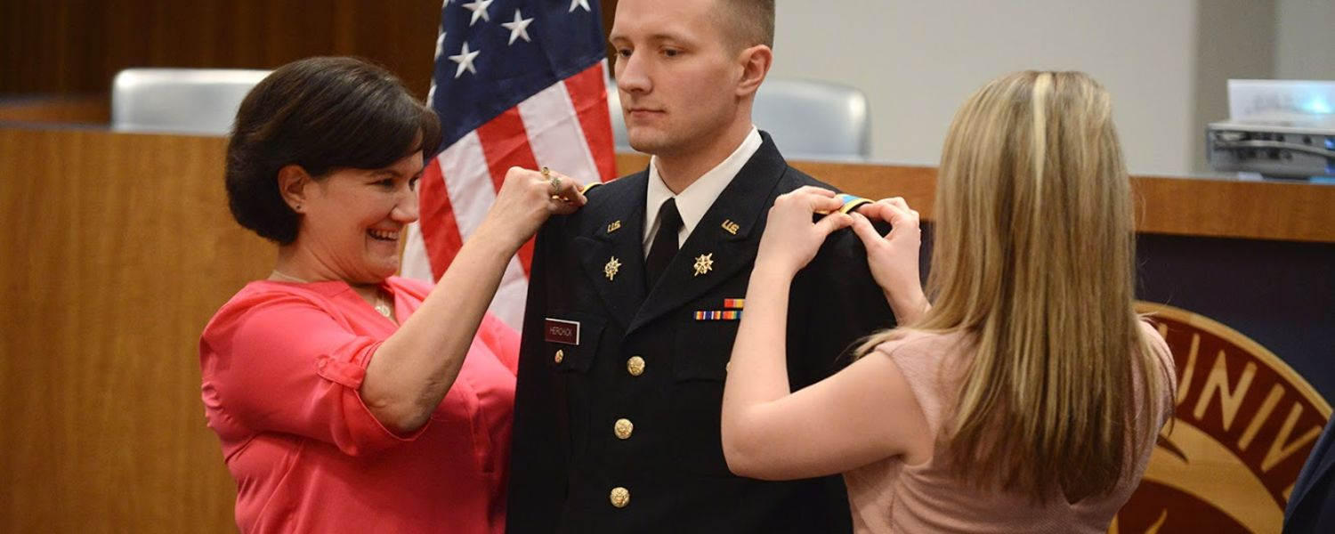 Newly commissioned U.S. Army 2nd Lt. David Herchick gets his bars pinned on by his mother on one side and his wife on the other during a commissioning ceremony.