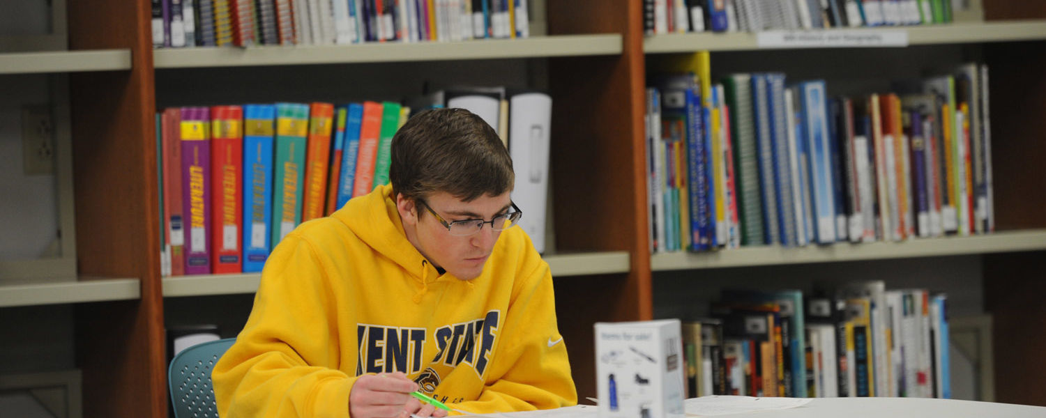 A Kent State student studies in the library area in White Hall.