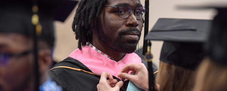 Graduate student preparing for commencement