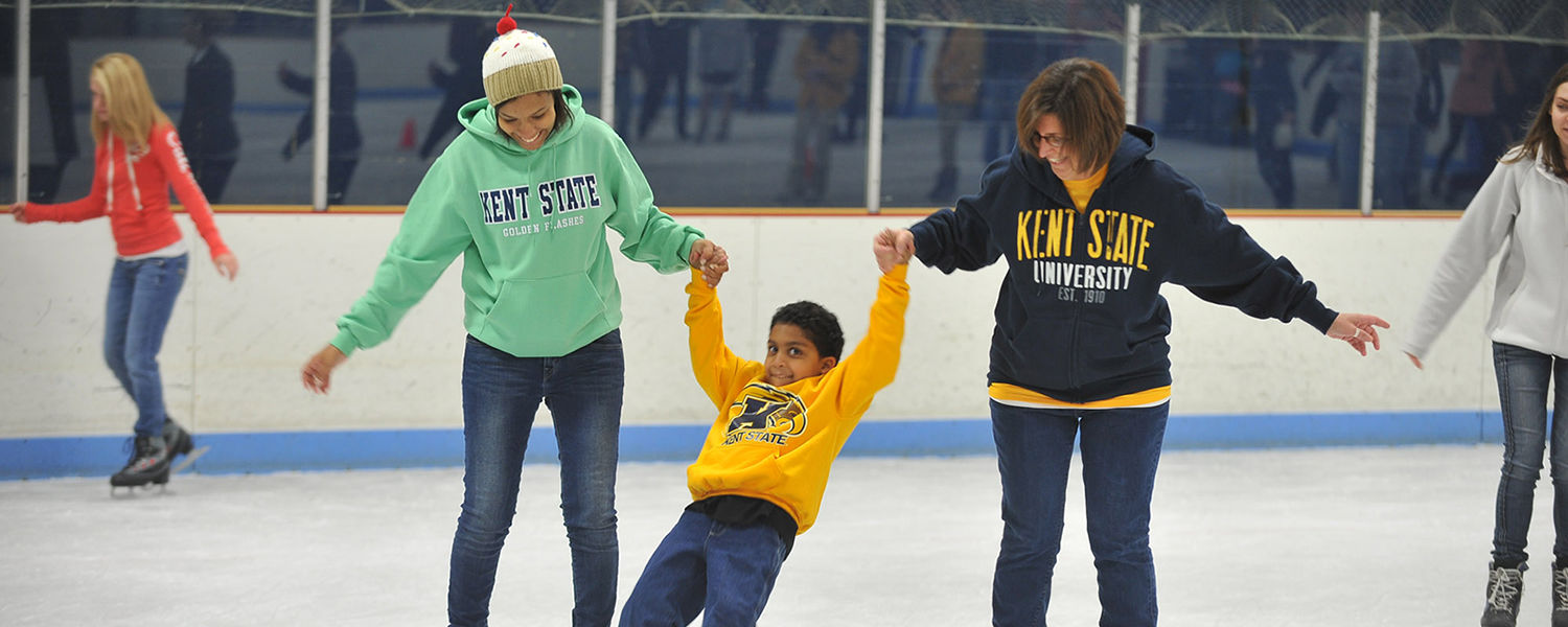 A little brother of a Kent State student gets some assistance to stay up on ice skates during Lil' Sibs Weekend.