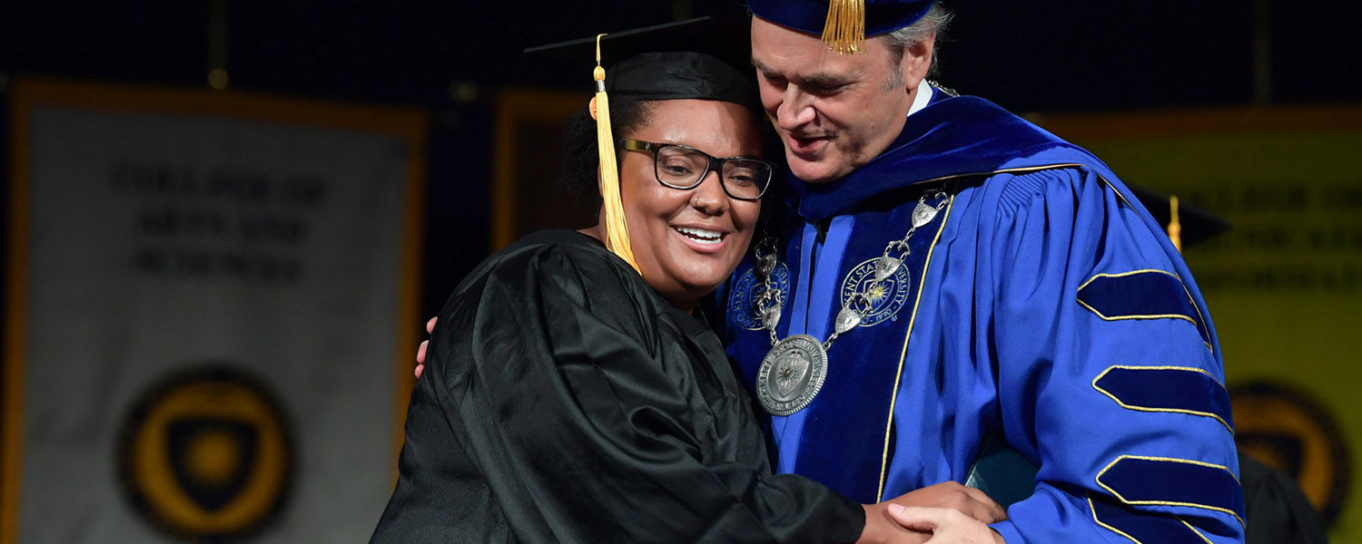 Kent State President Todd Diacon hugs a new graduate