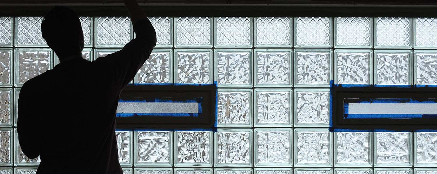 A Kent State student paints near a glass block window at the King Kennedy Community Center in Ravenna, Ohio.