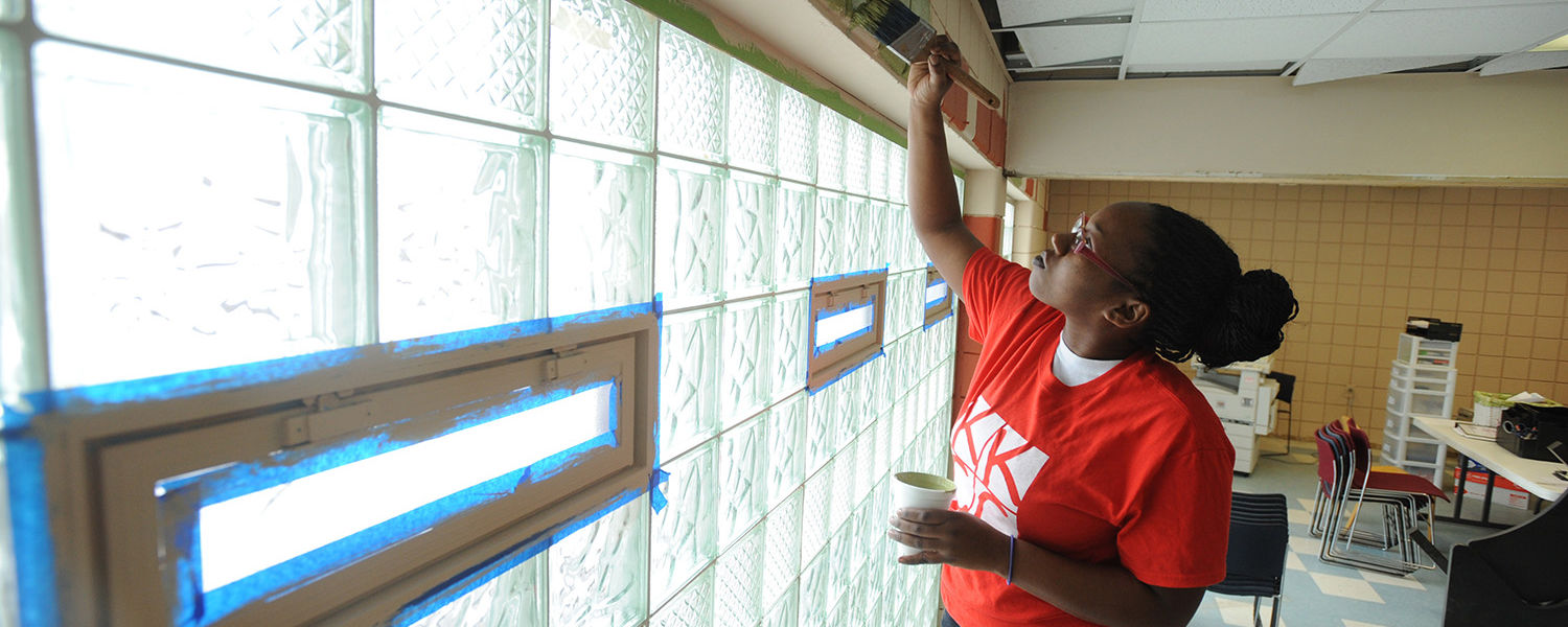 A Kent State student puts the finishing touches on the walls of the King Kennedy Community Center in Ravenna, Ohio.