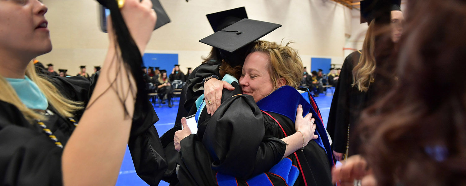 A professor from Kent State's College of Education, Health and Human Services hugs one of her graduate students during the advanced degree Commencement ceremony.