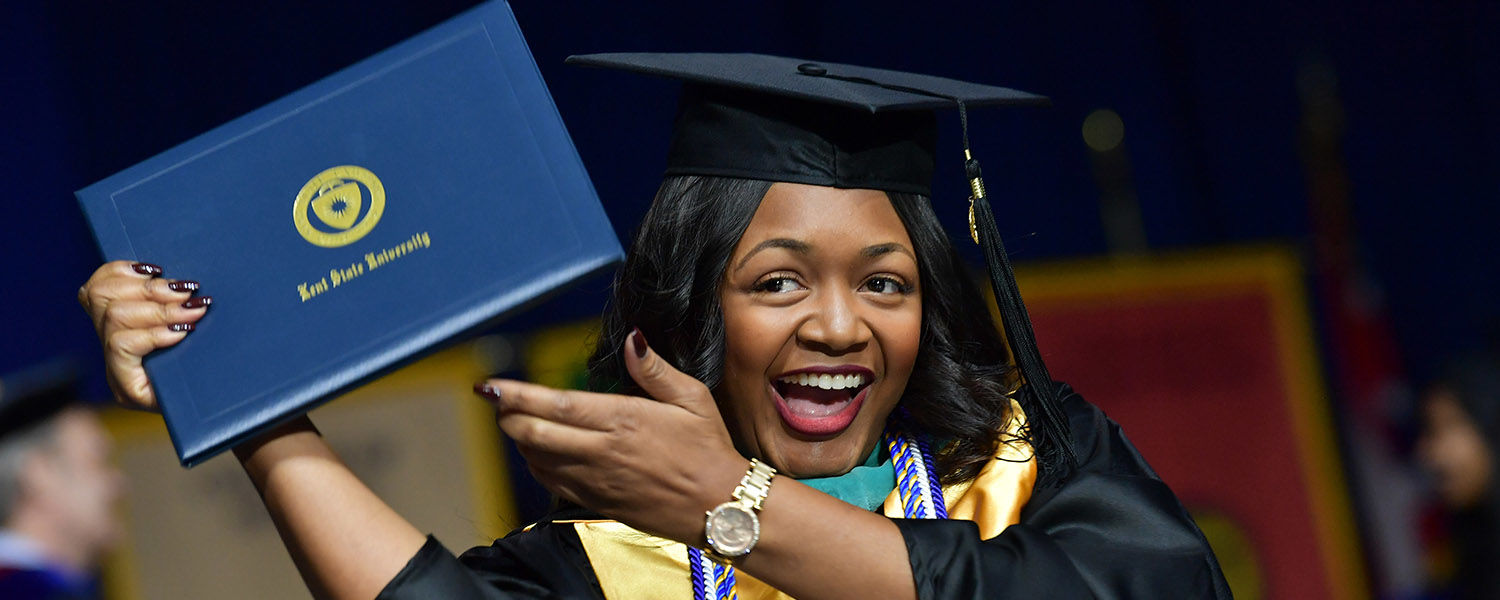 A graduate student proudly displays her diploma during Kent State's advanced degree Commencement ceremony.