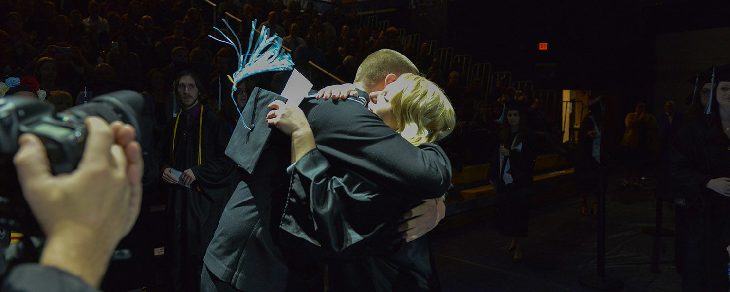 A member of the U.S. Navy surprises his graduating sister during her Commencement ceremony.